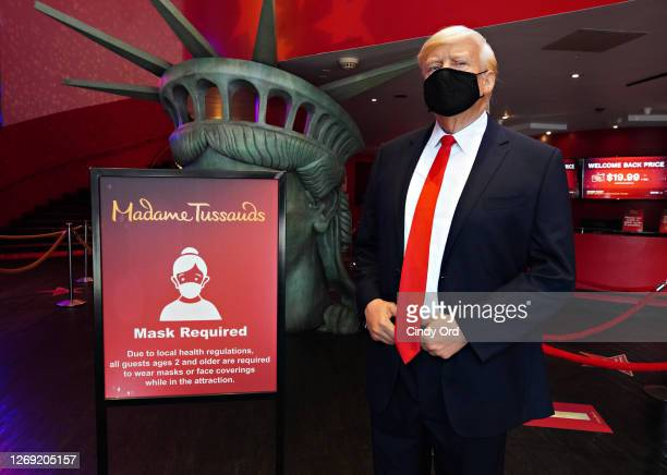Donald Trump figure wearing a protective mask stands next to a sign reading 'Mask Required' as Madame Tussauds New York re-opens to the public during...