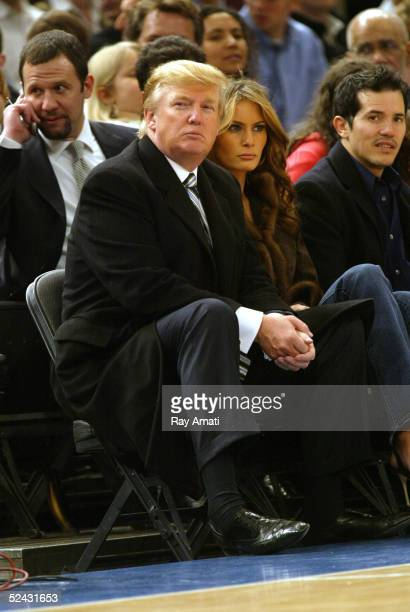 Donald Trump his wife Melania Trump and actor John Leguizamo sit courtside during the Miami Heat and New York Knicks NBA game on March 15 2005 at...