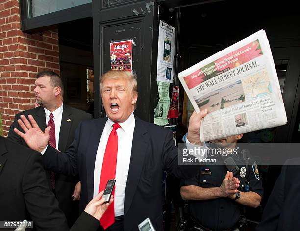 Donald Trump holding a copy of the Wall Street Journal while on a walking tour of Portsmouth NH with his private security people while campaigning on...