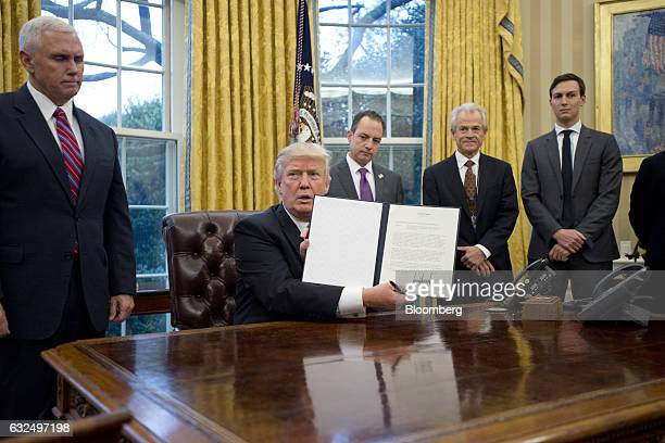 US Donald Trump holds up an executive order withdrawing the US from the TransPacific Partnership in the Oval Office of the White House in Washington...