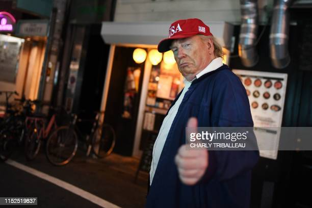 Donald Trump impersonator gives the thumb up as he walks in a street of Osaka during the G20 Osaka Summit on June 28, 2019.