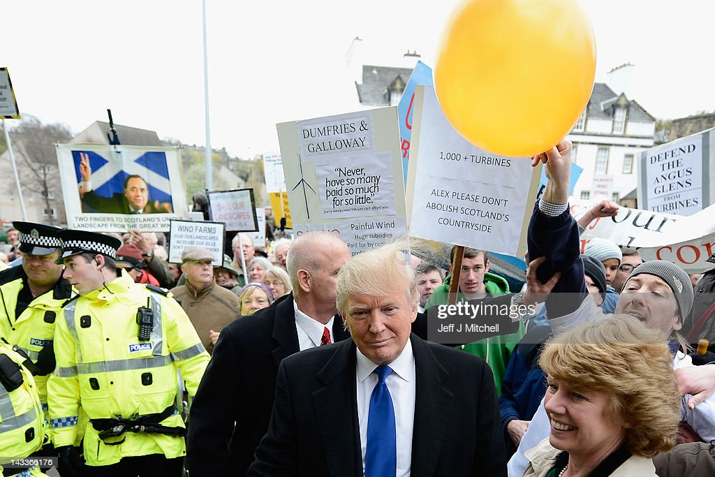 Donald Trump is hit on the head by a member of public holding a balloon following addressing the Scottish Parliament on April 25, 20012. Trump spoke of his concerns over a proposed wind farm, mooted to built near his new GBP 1 billion golf resor, telling the Scottish Parliament that they will destroy tourism in the country.