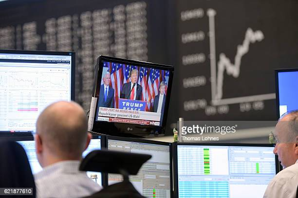 Donald Trump is seen on a TV screen below the graph showing the day's course of the DAX index at the Frankfurt Stock Exchange on November 9 2016 in...