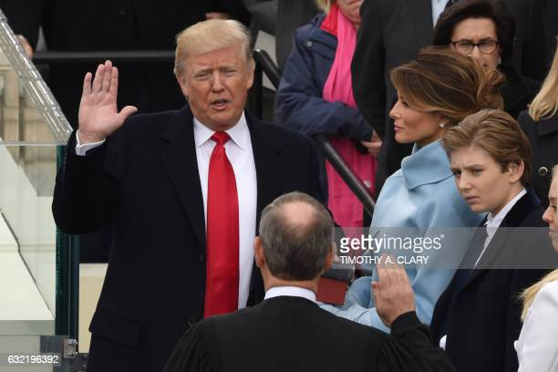 TOPSHOT Donald Trump is sworn in as the 45th US president by Supreme Court Chief Justice John Roberts in front of the Capitol in Washington on...