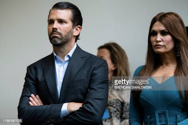 Donald Trump Jr and Kimberly Guilfoyle listen as the US president delivers remarks on citizenship and the census in the Rose Garden at the White...