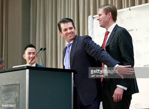 Donald Trump Jr grabs his brother Eric Trump on the arm during a ceremony for the official opening of the Trump International Hotel Tower on February...