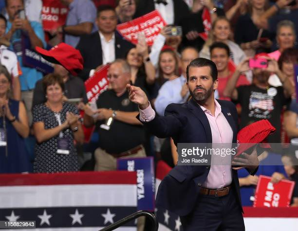 Donald Trump Jr tosses campaign hats to the crowd before his father Us President Donald Trump arrives on stage to announce his candidacy for a second...