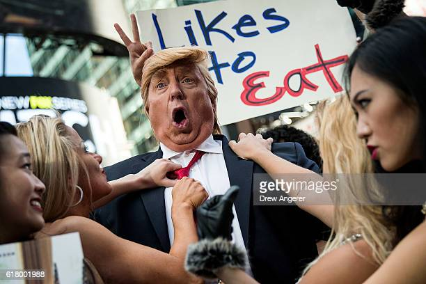 Donald Trump lookalike poses with bikiniclad women in Times Square October 25 2016 in New York City The stunt was organized by artist Alison Jackson