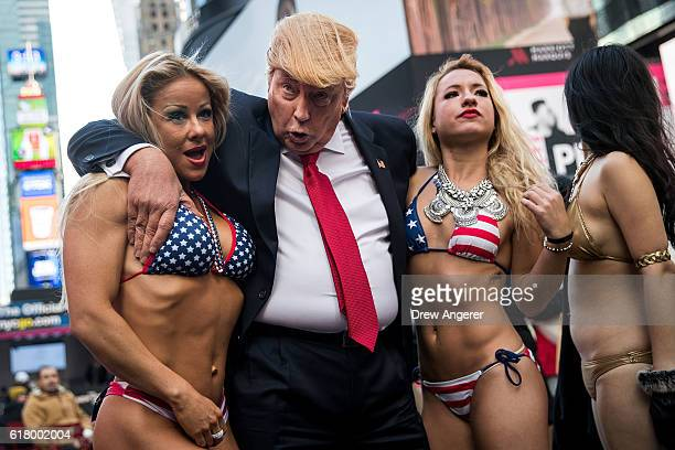 A Donald Trump lookalike poses with bikiniclad women in Times Square October 25 2016 in New York City The stunt was organized by artist Alison Jackson