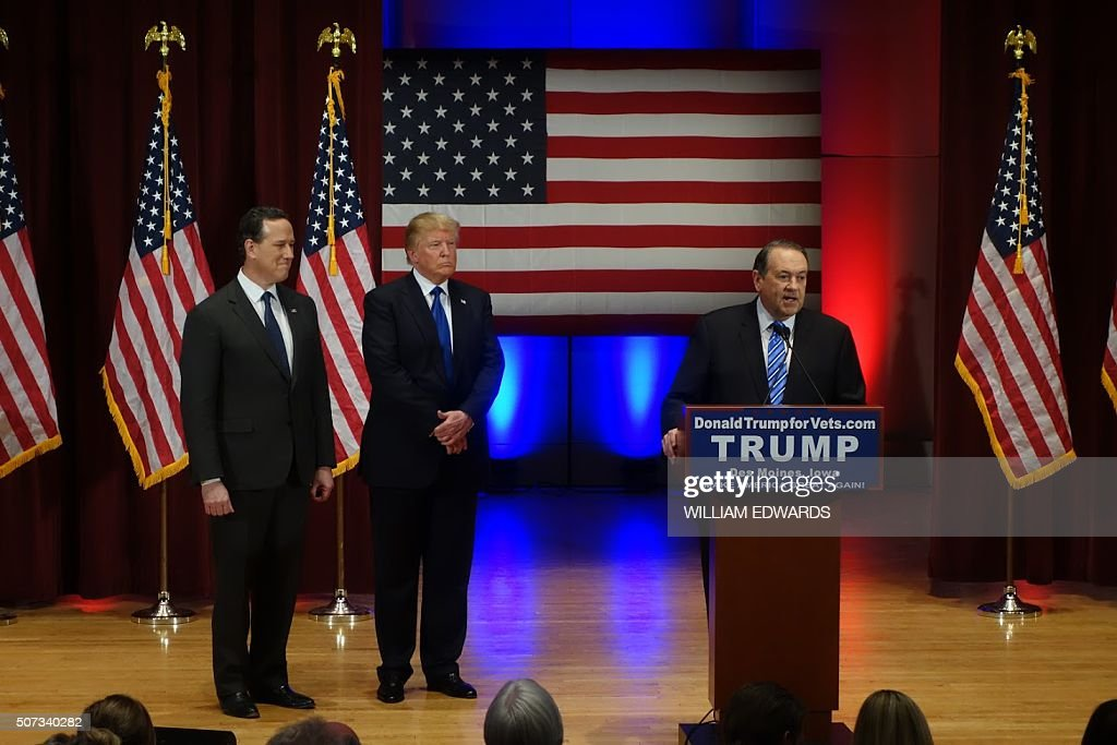 Donald Trump (C) looks on with Rick Santorm (L) as Mike Huckabee speaks during a Trump campaign rally raising funds for US military veterans at Drake University in Des Moines, Iowa on January 28, 2016. US Republicans scrambling to win the first contest in the presidential nomination race were gearing for battle at high-profile debate in Iowa, but frontrunner Donald Trump is upending the campaign by defiantly refusing to attend. Trump's gamble has left the presidential race in uncharted waters just days before Iowans vote on February 1, insisting he will not back down in his feud with debate host Fox News.Instead, the billionaire has doubled down, hosting a rogue, rival event for US military veterans at the same time that his own party is showcasing its candidates for president to all-important Iowa voters. / AFP / William EDWARDS