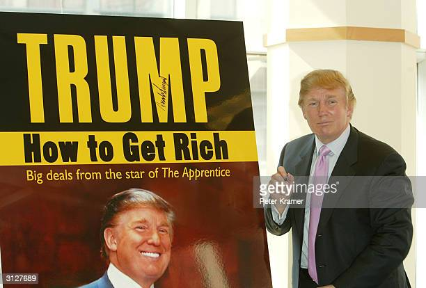 Donald Trump pauses for a moment after signing a poster depicting the over of his new book 'How To Get Rich' March 24 2004 at Barnes and Noble in...