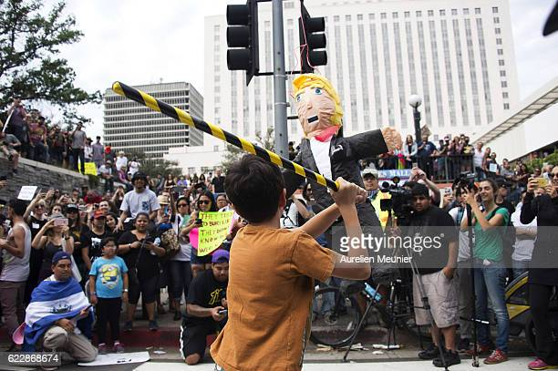 Donald Trump pinata is hit as thousands of people protest in the streets against Presidentelect Donald Trump in front of Federal Building on November...