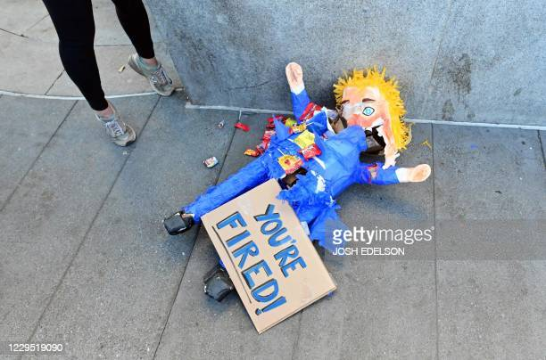 A Donald Trump pinata lays on the sidewalk after being broken open as people celebrate Joe Biden being elected President of the United States in the...