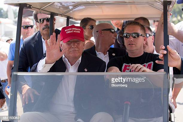 Donald Trump president and chief executive of Trump Organization Inc and 2016 Republican presidential candidate left rides a golf cart at the Iowa...