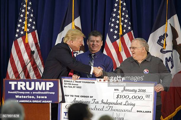 Donald Trump president and chief executive of Trump Organization Inc and 2016 Republican presidential candidate left presents a check for $100000 to...
