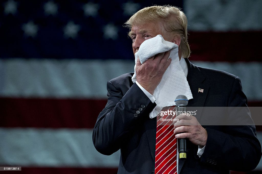 Donald Trump, president and chief executive of Trump Organization Inc. and 2016 Republican presidential candidate, wipes his face while listening to a question during a town hall event at the Tampa Convention Center in Tampa, Florida, U.S., on Monday, March 14, 2016. As protesters shadow campaign appearances by Trump, the billionaire has shifted a planned Monday-night rally in south Florida to Ohio, where polls show Governor John Kasich may be pulling ahead days before the states primary election. Photographer: Andrew Harrer/Bloomberg via Getty Images
