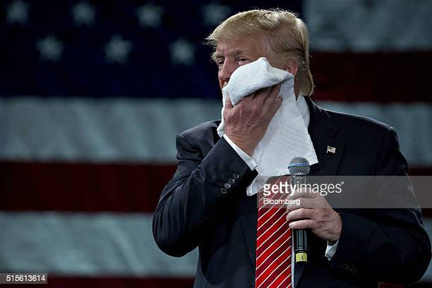 Donald Trump president and chief executive of Trump Organization Inc and 2016 Republican presidential candidate wipes his face while listening to a...