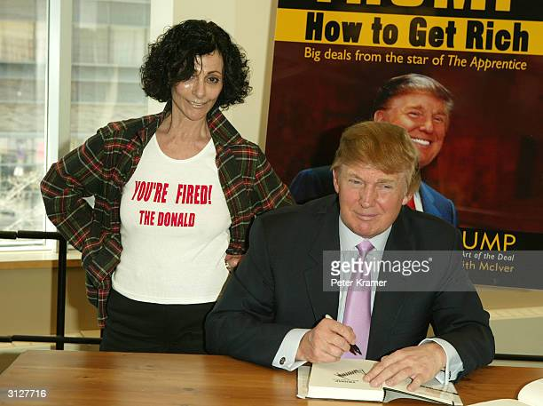 Donald Trump signs a copy of his new book 'How To Get Rich' for a fan March 24 2004 at Barnes and Noble in Lincoln Center in New York City