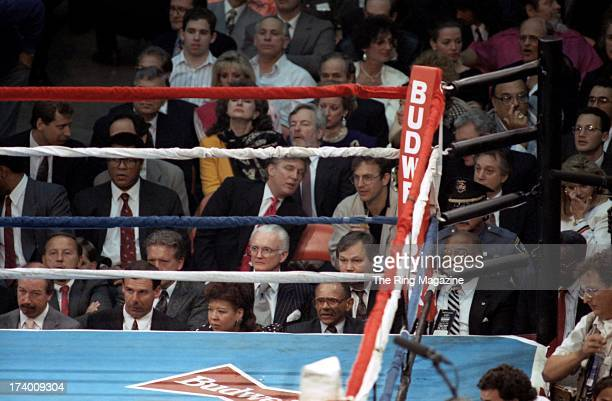 Donald Trump sits between Muhammad Ali and actor Kevin Costner as they watch the fight between Evander Holyfield and George Foreman at Convention...