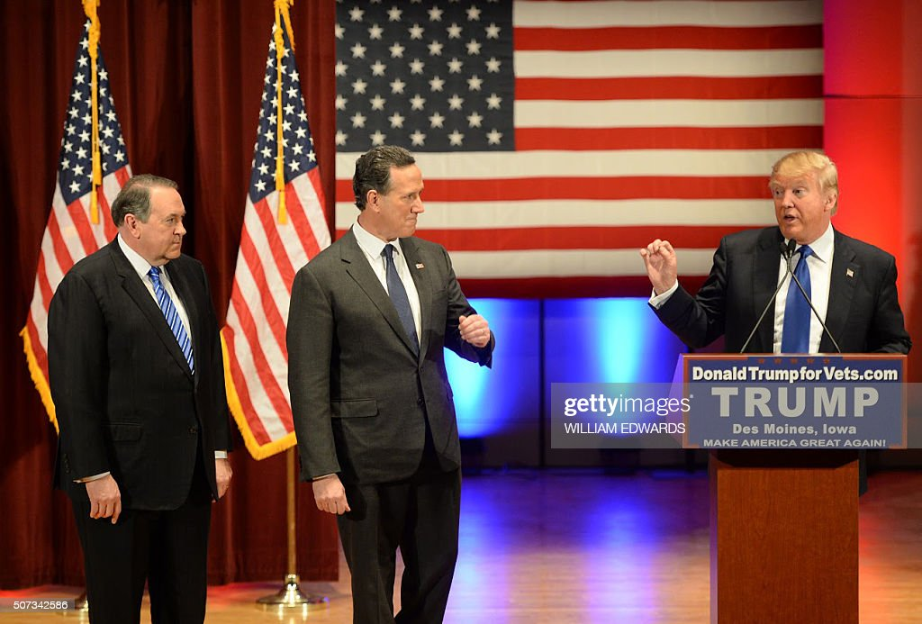 Donald Trump (R) speaks as Rick Santorm (C) as Mike Huckabee (L) look on during a Trump campaign rally raising funds for US military veterans at Drake University in Des Moines, Iowa on January 28, 2016. US Republicans scrambling to win the first contest in the presidential nomination race were gearing for battle at high-profile debate in Iowa, but frontrunner Donald Trump is upending the campaign by defiantly refusing to attend. Trump's gamble has left the presidential race in uncharted waters just days before Iowans vote on February 1, insisting he will not back down in his feud with debate host Fox News.Instead, the billionaire has doubled down, hosting a rogue, rival event for US military veterans at the same time that his own party is showcasing its candidates for president to all-important Iowa voters. / AFP / William EDWARDS