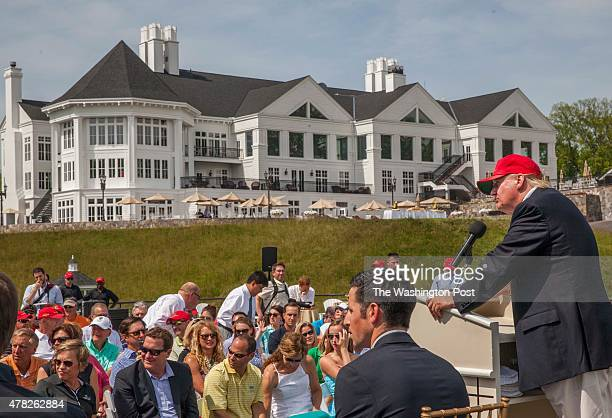 Donald Trump speaks in the celebration of the opening of his championship golf course with their golf pro Kevin Morris seated next to him in Sterling...
