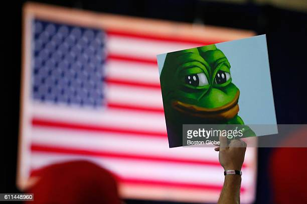 Donald Trump supporter holds a cartoon designated a hate symbol by the antidefamation league before the start of a campaign event in Bedford NH on...