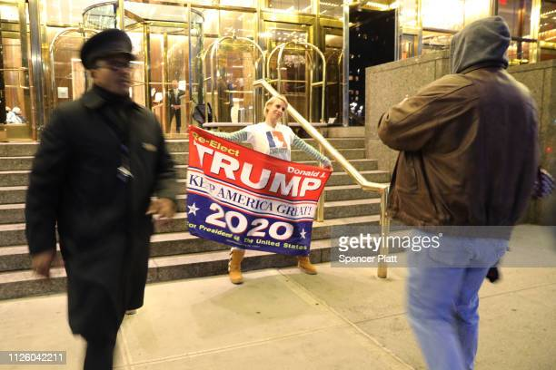 Donald Trump supporter holds up a banner as protesters calling for the impeachment of Trump demonstrate in front of the Trump International Hotel on...