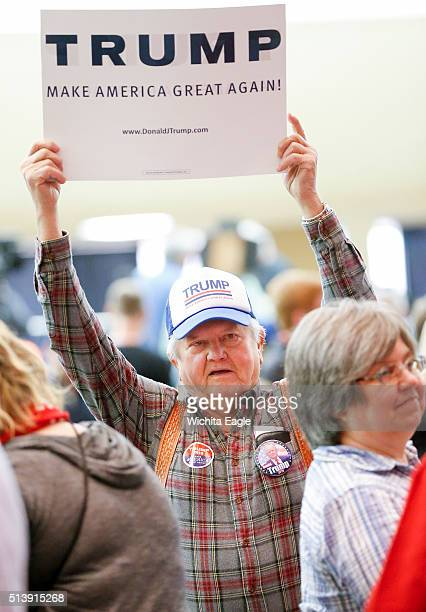 A Donald Trump supporter raises his sign inside Century II where the Republican presdential caucus took place in Wichita Kan on Saturday March 5 2016