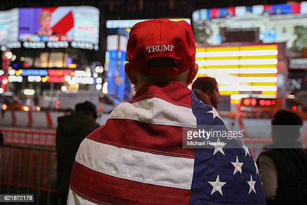 Donald Trump supporter watches the screens outside Times Square Studios as he awaits the results of the US presidental election on November 9 2016 in...