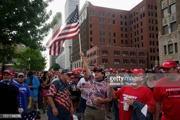 Donald Trump supporters cheer and wave an American flag in the waiting area prior to a campaign rally for President Donald Trump on June 20 2020 in...