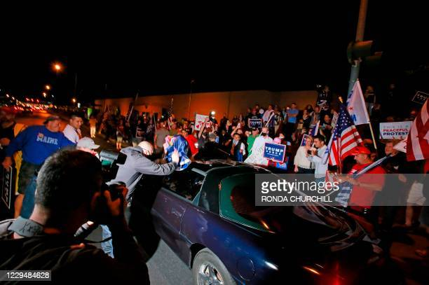 Donald Trump supporters get into an altercation with a driver that stopped to voice his support of Joe Biden during a protest about the Nevada vote...