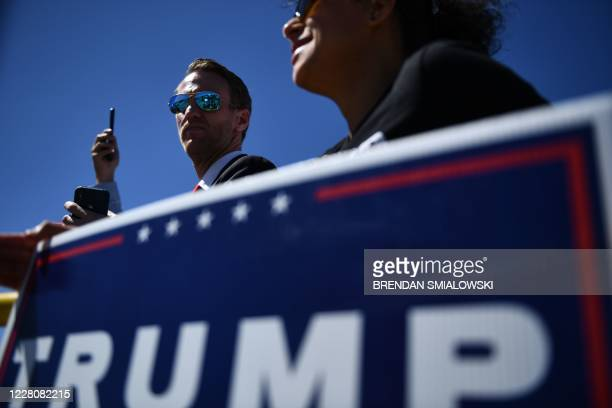 Donald Trump supporters hold up banners on August 17, 2020 in Minneapolis, Minnesota as the US president delivers remarks on jobs and the economy on...