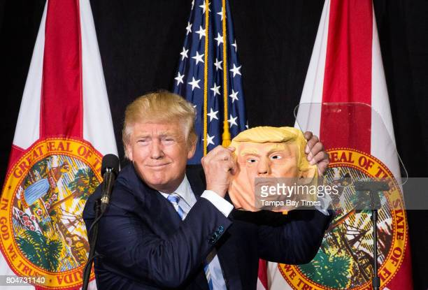 Donald Trump takes a break from speaking to compare his face to a mask during a rally at the Sarasota Fairgrounds in Sarasota Florida on Monday...