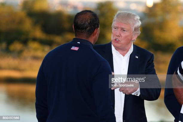 Donald Trump the 45th president of the United States talks to USA vice captain Tiger Woods after the final round of the Presidents Cup at Liberty...