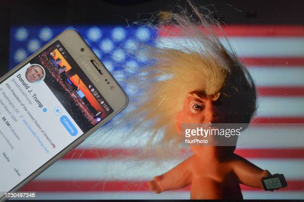 Donald Trump's Twitter account displayed on a mobile phone screen next to a vinyl doll which features the U.S. President Donald Trump, seen in front...