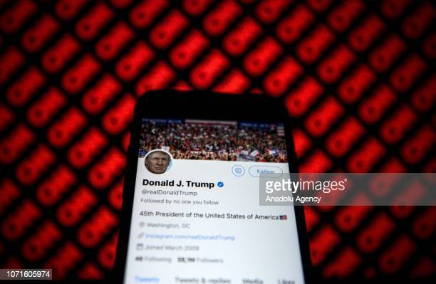 Donald Trump's Twitter profile is seen on a smartphone against a backdrop with the CNN logo in Ankara Turkey on December 9 2018