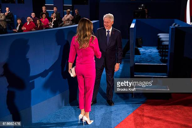 Donald Trump's wife Melania Trump shakes hands with former US President Bill Clinton before the town hall debate at Washington University in St Louis...