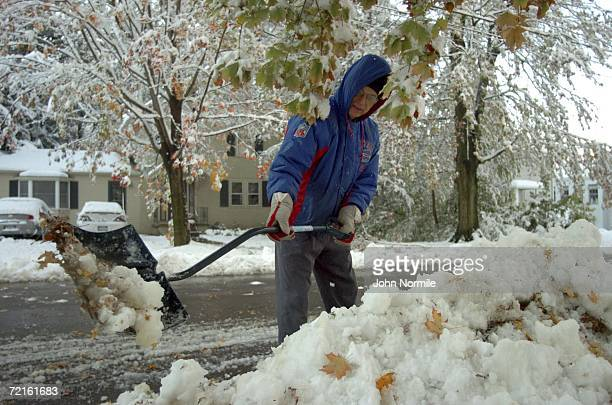 Donald Webber clears snow October 13, 2006 outside of Buffalo in Orchard Park, New York. A rare and record breaking early season snowfall closed a...