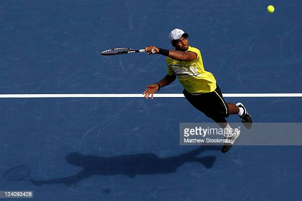 Donald Young of the United States returns a shot against Andy Murray of Great Britain returns a shot against during Day Eleven of the 2011 US Open at...