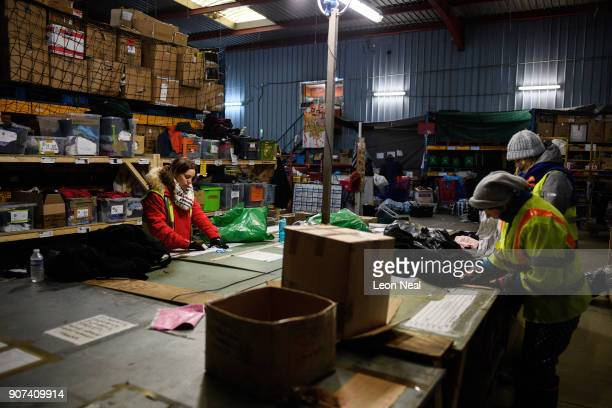 Donated clothes are sized and sorted at the 'Help Refugees' charity warehouse on January 19 2018 in Calais France During a visit to the UK by French...