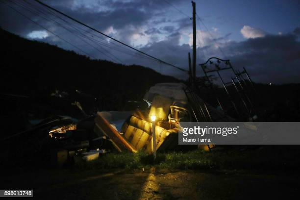 A donated solar lamp in a driveway illuminates storm debris still waiting to be collected on Christmas day on December 25 2017 in Morovis Puerto Rico...