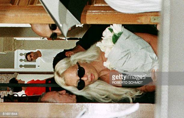Donatella Versace the sister of slain Italian designer Gianni Versace carries some flowers as she leaves her brothers' house through a back door in...