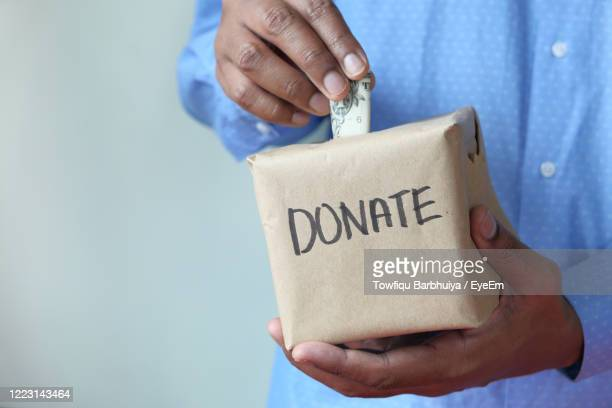 donating for corona virus. man puts donation in a box with copy space - giving tuesday stock pictures, royalty-free photos & images