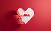 Donation Concept- Donate Text Inside Of A Red Folding Heart Shape On White Background