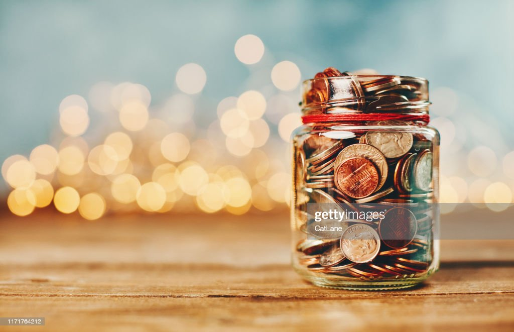 Donation money jar filled with coins in front of holiday lights : Stock Photo