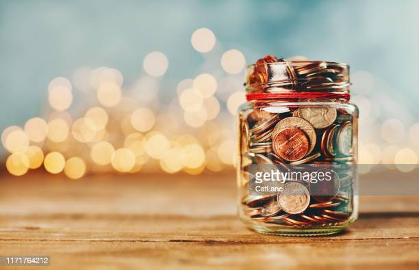 donation money jar filled with coins in front of holiday lights - investment stock pictures, royalty-free photos & images