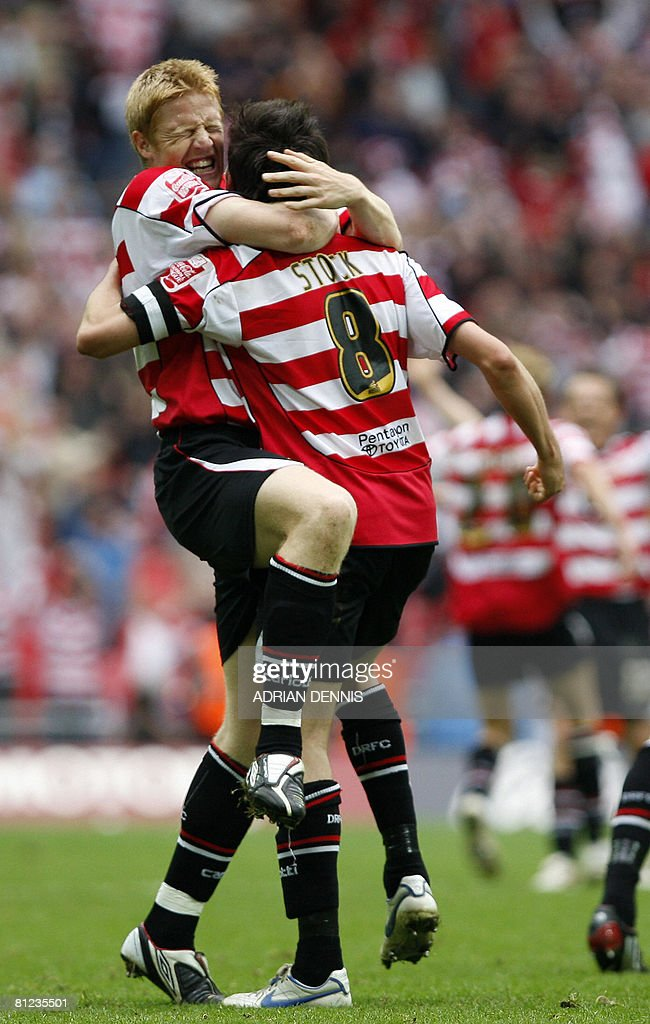 Doncaster Rovers' Adam Lockwood (L) and Captain Brian Stock (C) celebrate their victory over Leeds United during the Football League One playoff final football match at Wembley Stadium in London on May 25, 2008. Doncaster won the game 1-0 to secure promotion to the Championship. AFP PHOTO / Adrian Dennis