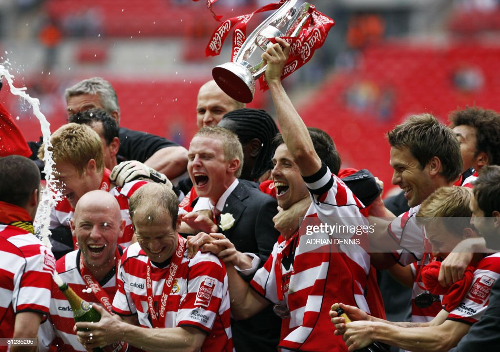 Doncaster Rovers' Captain Brian Stock (C) holds the trophy aloft as they celebrate their victory over Leeds United during the Football League One playoff final football match at Wembley Stadium in London on May 25, 2008. Doncaster won the game 1-0 to secure promotion to the Championship. AFP PHOTO / Adrian Dennis
