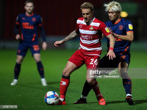 Doncaster Rovers' James Coppinger shields the ball from Blackpool's Kenneth Dougall during the Sky Bet League One match between Doncaster Rovers and...