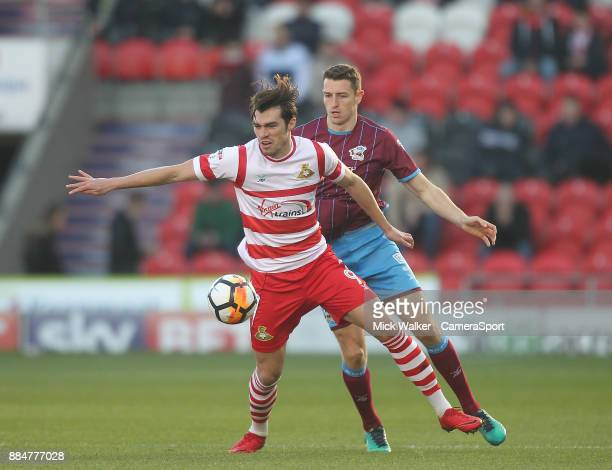 Doncaster Rovers' John Marquis battles with Scunthorpe Utd's Murray Wallace during the Sky Bet League One match between Doncaster Rovers and...